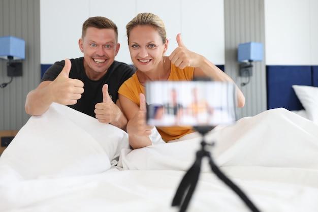 Junge blogger von männern und frauen halten daumen hoch und schauen sich das kamera-blogging-konzept an