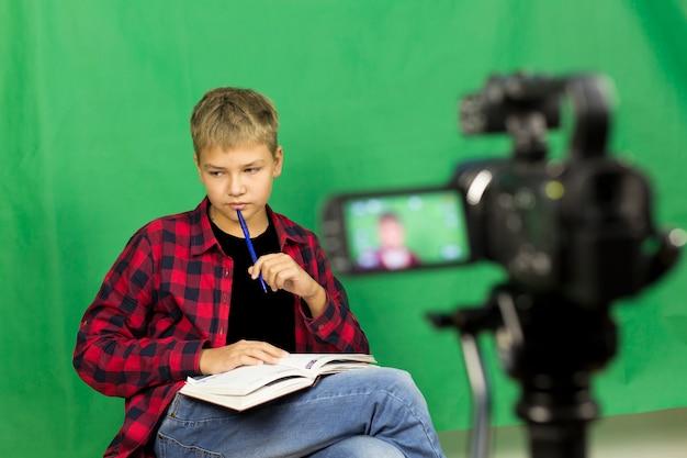 Junge blogger zeichnet video auf einem grün auf