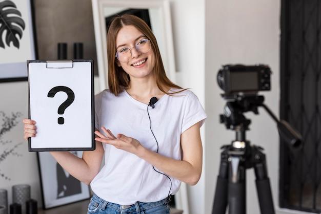 Junge bloggeraufzeichnung mit professioneller kamera, die zwischenablage mit fragezeichen hält
