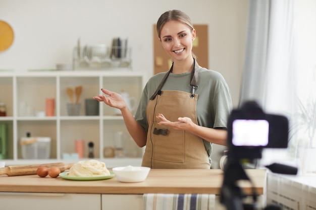 Junge bloggerin, die schürze trägt und ihren anhängern beibringt, online in der häuslichen küche zu kochen