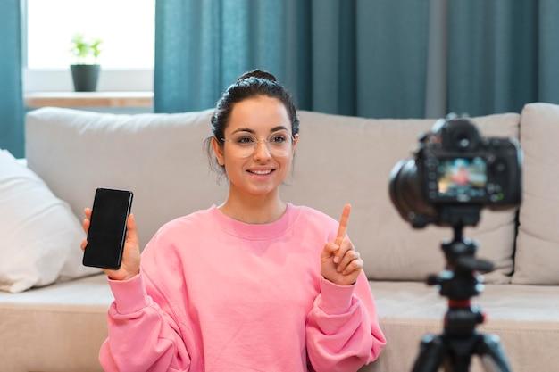 Junge bloggerin, die sich mit dem telefon in der hand aufzeichnet