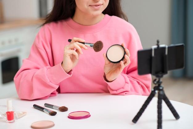 Junge bloggerin, die sich mit make-up aufzeichnet