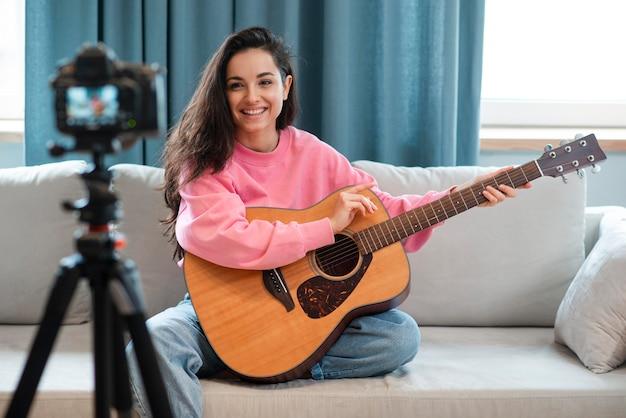 Junge bloggerin, die sich selbst aufzeichnet und zeigt, wie man gitarre spielt