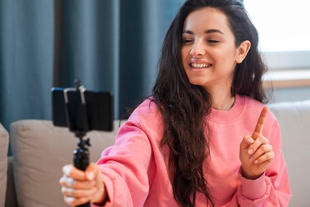 Junge bloggerin hält ihr smartphone und finger hoch