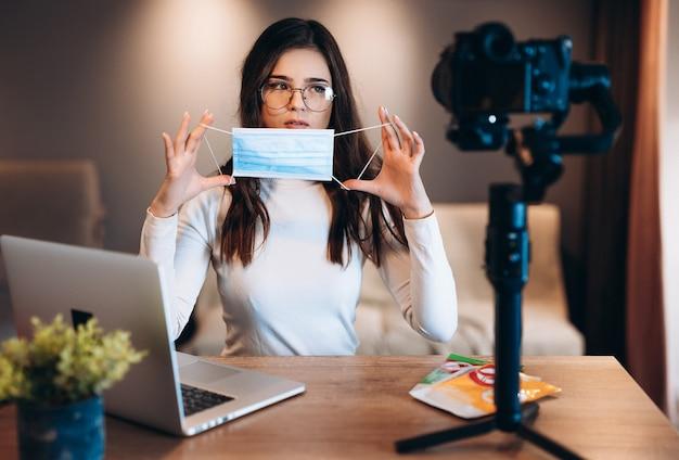 Junge bloggerin in brille weiblich filmt ihren vlog und zeigt ihrem publikum, dass es sicher ist und eine medizinische maske benutzt. coronovirus-konzept für einen sicheren arbeitsplatz. medizinische maske auf gesicht setzen.