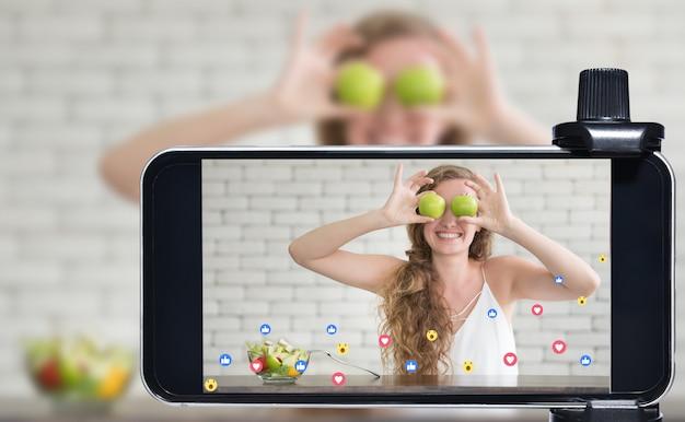 Junge bloggerin und vloggerin und online-influencerin live streaming einer kochshow in sozialen medien mit einem smartphone