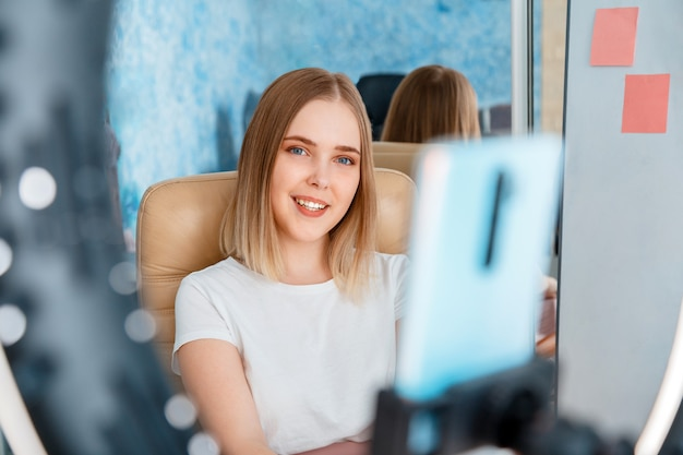 Junge bloggerin zeichnet live-videoinhalte auf, die live an abonnenten mit handy und ringlichtlampe übertragen werden. teenager-mädchen lächelt und spricht