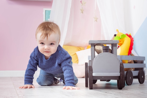 Junge blond in einem blauen pullover kriecht auf einem holzboden. einjähriges baby, das mit holzspielzeug spielt.