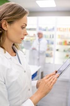 Junge blonde apothekerin, die daten auf dem display der digitalen tablette durchsieht, während sie informationen über neue medikamente bei der arbeit lernt