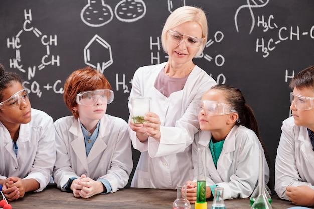 Junge blonde chemielehrerin im weißkittel zeigt ihren schülern eine mischung aus zwei chemischen substanzen, während sie gemeinsam über die reaktion diskutiert