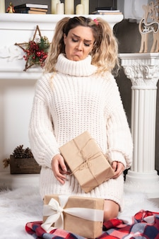 Junge blonde dame, die geschenke betrachtet, die nahe dem kamin stehen.