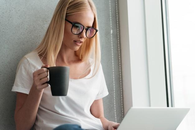 Junge blonde dame, die zu hause laptop verwendet und tee trinkt