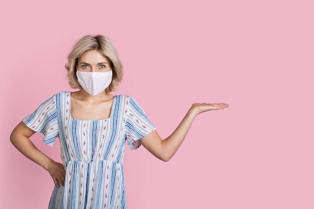 Junge blonde dame in einem kleid, das eine medizinische maske trägt, wirbt etwas auf einer rosa wand, die mit handfläche ist