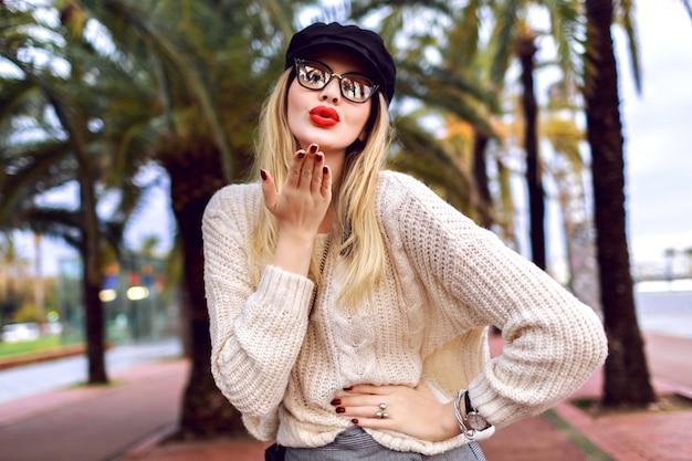 Junge blonde elegante stilvolle frau, die kuss sendet und auf barcelona straße mit palmen aufwirft, kuscheligen pullover, mütze und klare brille tragend, modestil, reisestimmung, frühlingszeit.