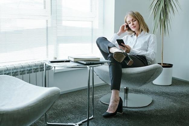 Junge blonde entspannte geschäftsfrau in der abendgarderobe, die im sessel durch großes bürofenster sitzt und in der pause im smartphone scrollt