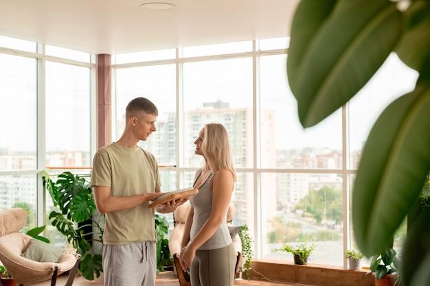 Junge blonde fit frau in aktivkleidung, die personal trainer betrachtet, der sie über zeitgenössischen yoga-ausbildungskurs im freizeitzentrum berät