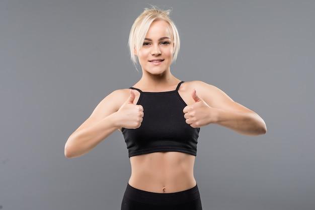 Junge blonde fit sportliche mädchen frau daumen hoch in schwarzer sportbekleidung demostrieren ihren starken muskulösen körper