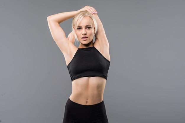 Junge blonde fit sportliche mädchenfrau in schwarzer sportbekleidung demostriert ihre starke muskulöse körperdehnung