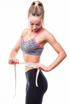 Junge blonde fitness-frau, die ihren körper mit dem lineal misst, das in fasion sportswear gekleidet ist, gewicht-konzept zu verlieren