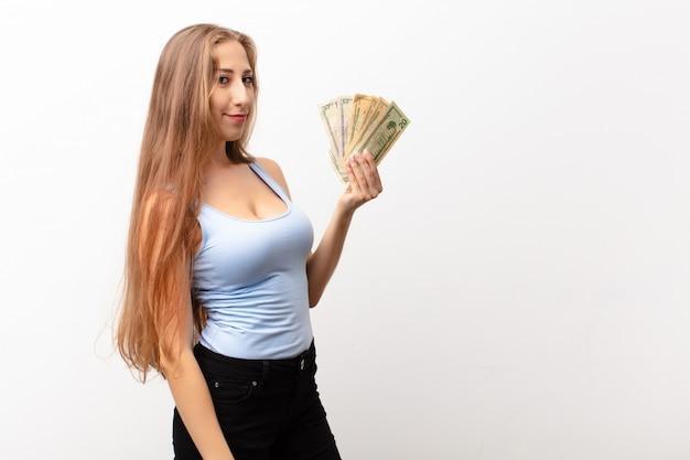 Junge blonde frau auf profilansicht, die raum voraus kopiert, denkt, sich vorstellt oder träumt, dollar-banknoten zu halten