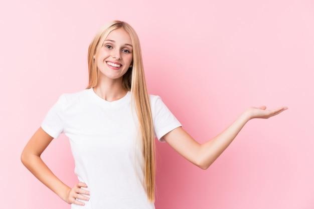 Junge blonde frau auf rosa hintergrund, der einen kopienraum auf einer handfläche zeigt und eine andere hand auf taille hält.