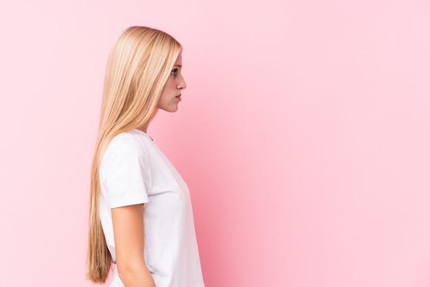 Junge blonde frau auf rosa wand, die links schaut, seitwärts darstellen.