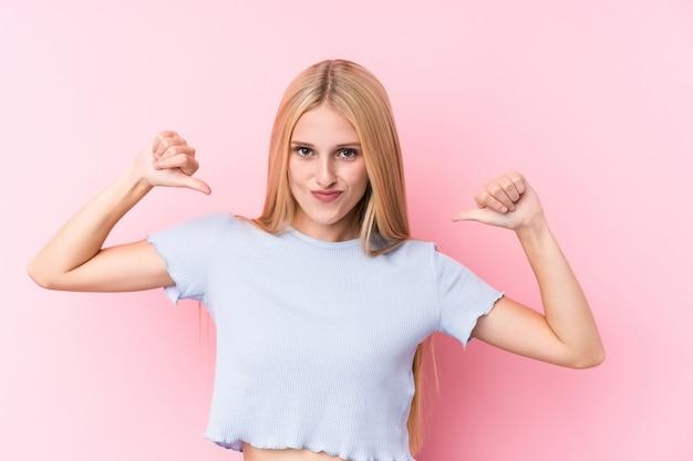 Junge blonde frau auf rosa wand fühlt sich stolz und selbstbewusst, beispiel zu folgen.