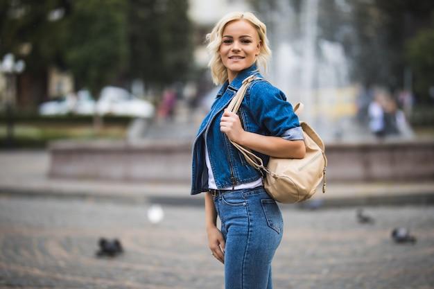 Junge blonde frau auf straßenwegquadrat-fontain, gekleidet in blue jeans suite mit tasche auf ihrer schulter in sonnigem tag