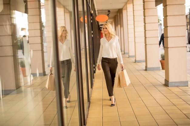 Junge blonde frau beim einkaufen auf einer straße