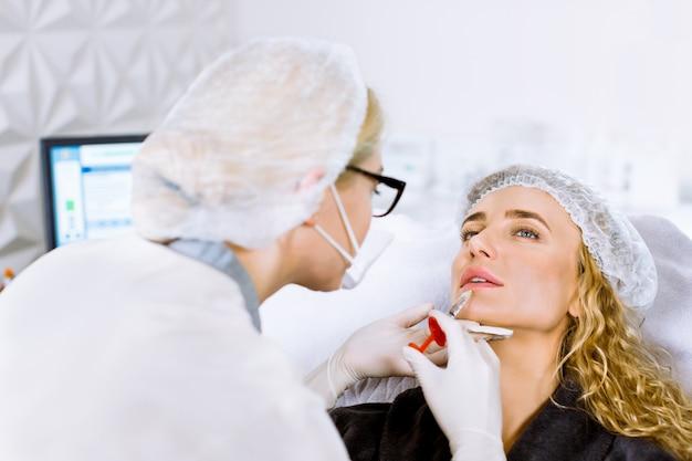 Junge blonde frau bekommt eine spritze in die lippen im schönheitssalon. schönheitsinjektionen - frau, die im büro der kosmetikerin liegt.