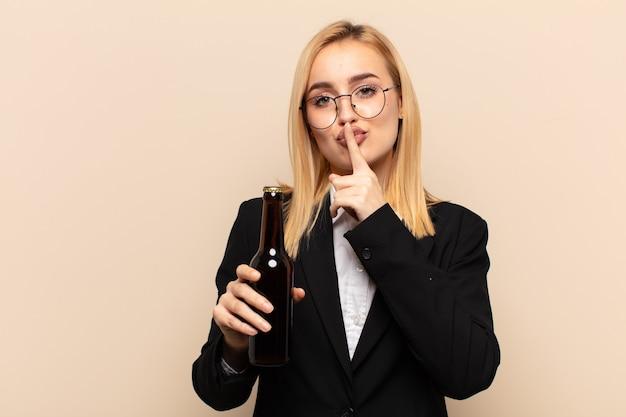 Junge blonde frau bittet um stille und ruhe, gestikuliert mit dem finger vor dem mund, sagt shh oder hält ein geheimnis
