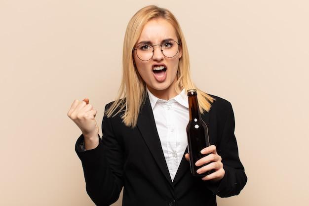 Junge blonde frau, die aggressiv mit einem wütenden ausdruck oder mit geballten fäusten schreit, um erfolg zu feiern