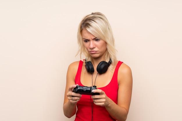 Junge blonde frau, die an den videospielen spielt