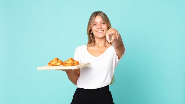 Junge blonde frau, die auf die kamera zeigt, die dich auswählt und ein croissant-tablett hält
