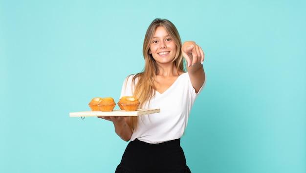 Junge blonde frau, die auf die kamera zeigt, die dich auswählt und einen muffins-troy hält
