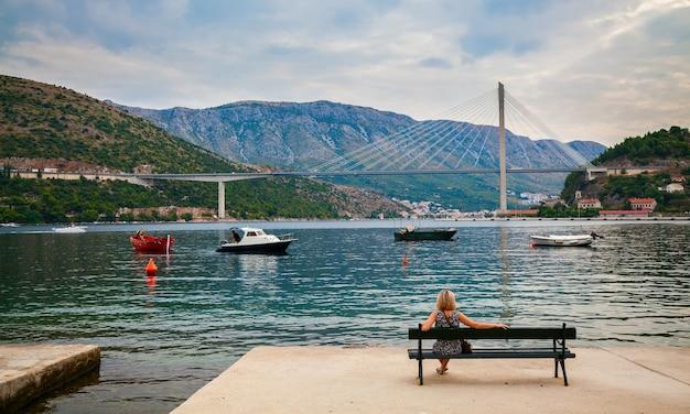 Junge blonde frau, die auf einer bank sitzt und die tudjman-brücke in dubrovnik, kroatien betrachtet