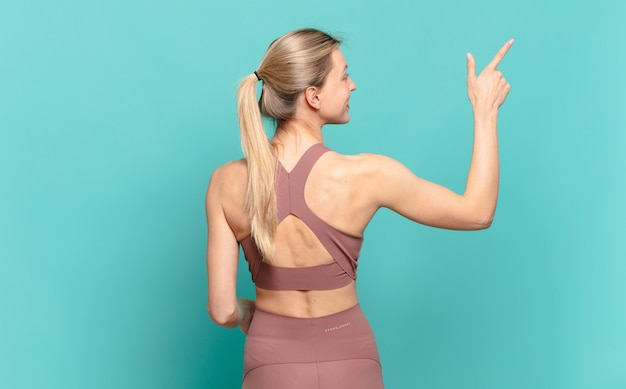 Junge blonde frau, die auf kopienraum, rückansicht steht und auf objekt zeigt. sportkonzept