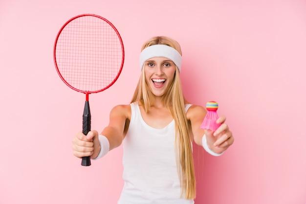 Junge blonde frau, die badminton spielt