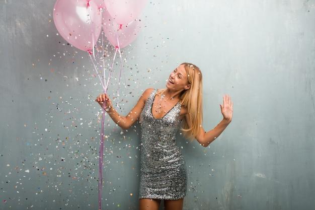 Junge blonde frau, die ballone des neuen jahres halten feiert.