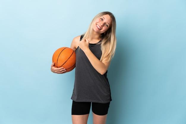 Junge blonde frau, die basketball spielt, lokalisiert auf blauer wand, die einen sieg feiert