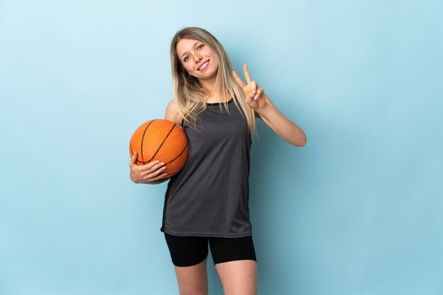 Junge blonde frau, die basketball spielt, lokalisiert auf der blauen wand lächelnd und siegeszeichen zeigend