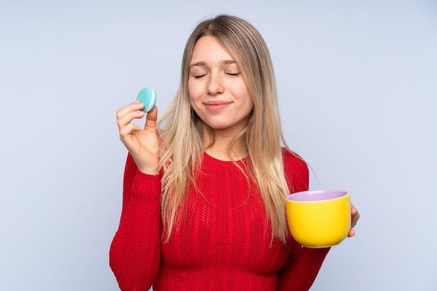 Junge blonde frau, die bunte französische macarons und eine tasse milch hält