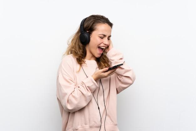 Junge blonde frau, die das mobile mit kopfhörern verwendet und singt