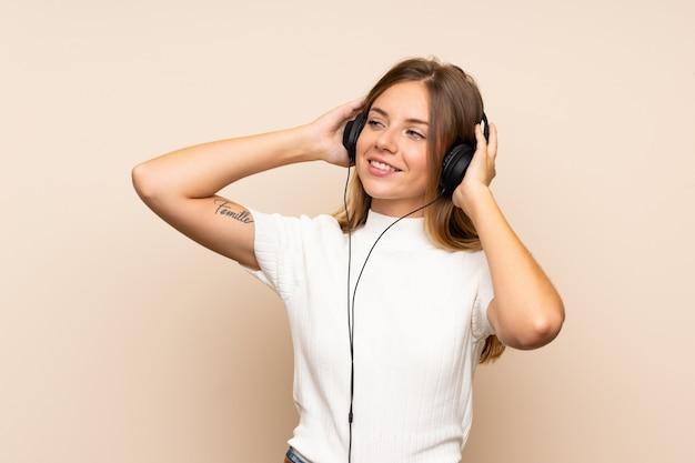 Junge blonde frau, die das mobile mit kopfhörern verwendet