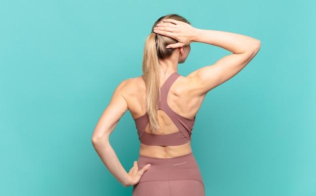 Junge blonde frau, die denkt oder zweifelt, den kopf kratzt, sich verwirrt und verwirrt fühlt, rück- oder rückansicht. sportkonzept