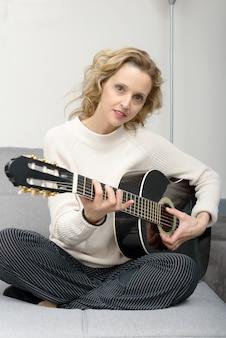 Junge blonde frau, die die akustische gitarre spielt