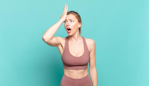 Junge blonde frau, die die handfläche zur stirn hebt und denkt, oops, nachdem sie einen dummen fehler gemacht oder sich erinnert hat, sich dumm zu fühlen