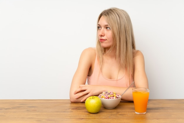 Junge blonde frau, die die schauende seite frühstückt