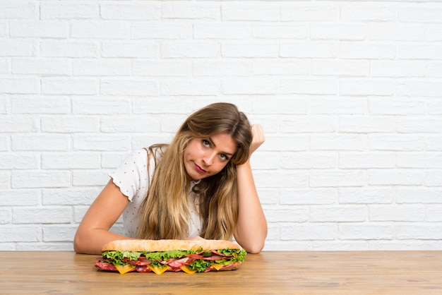 Junge blonde frau, die ein großes sandwich anhält