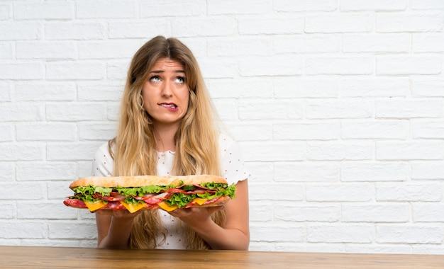 Junge blonde frau, die ein großes sandwich hat zweifel anhält